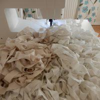 En hög med mattrasor bakom symaskinen