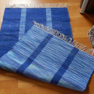 Trasmatta som är tvåsidig med längsgående ränder i ljus och mörk blå färg.